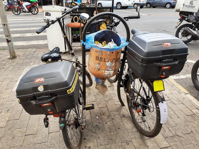 Bicicleta parada ao lado de moto  Descrição gerada automaticamente