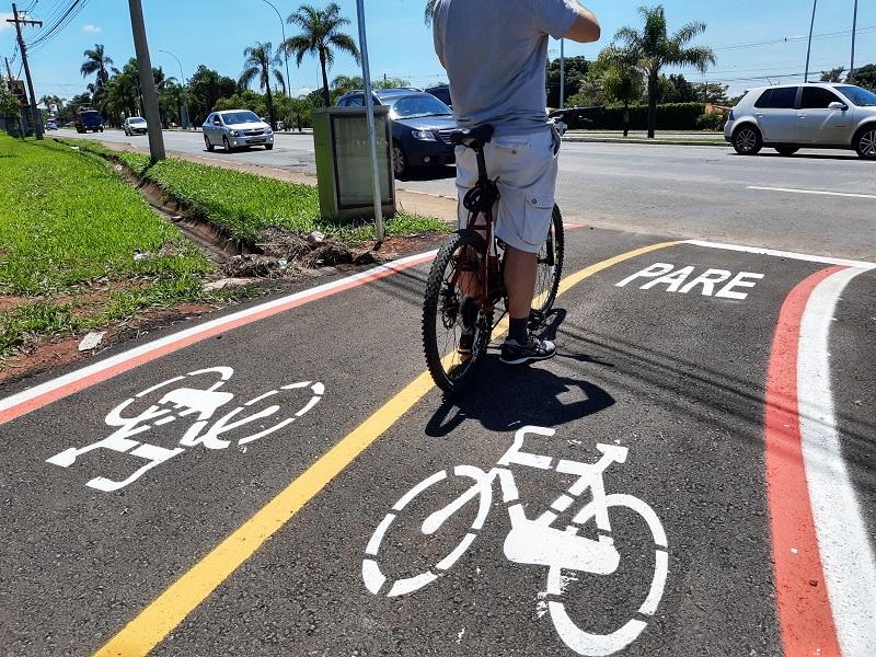 Homem andando de bicicleta na rua  Descrição gerada automaticamente