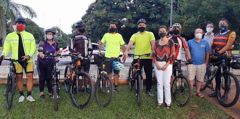 Grupo de pessoas posando para foto com bicicleta  Descrição gerada automaticamente