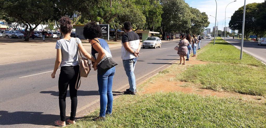Pessoas andando na calçada com grama  Descrição gerada automaticamente