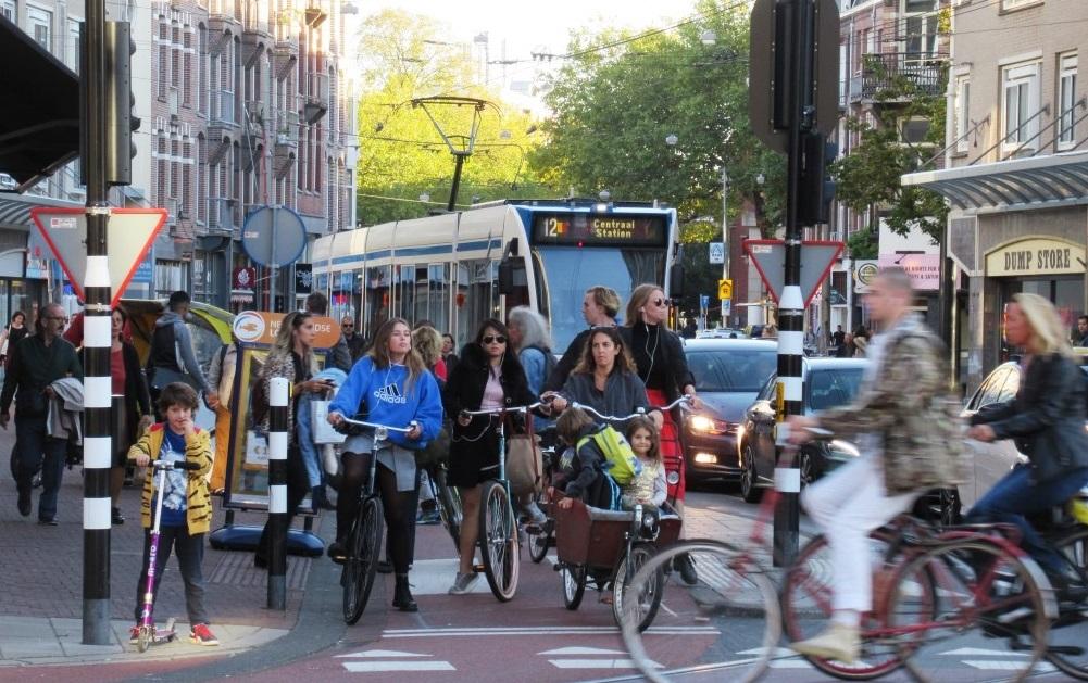 Pessoas andando de bicicleta na rua  Descrição gerada automaticamente