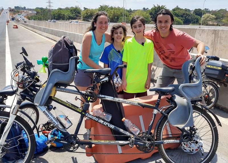 Pessoas posando para foto com bicicleta  Descrição gerada automaticamente
