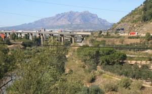 Pista para carros, linha de trem e trilha ao longo do rio. No fundo as montanhas de Montserrat