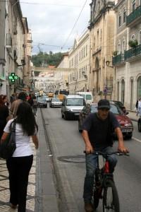 Ciclista se aventura nas ruas de Coimbra, entre a guia, uma tampa de bueiro e os carros