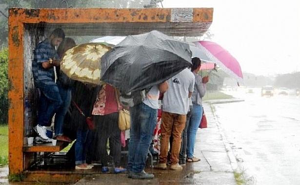 Abrigo de ônibus superlotado em dia chuvoso
