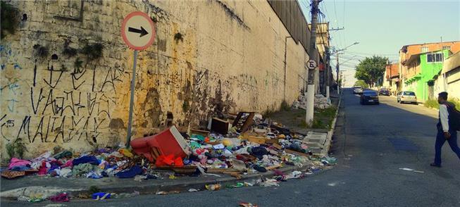 Cena comum: calçada ocupada por lixo e entulho