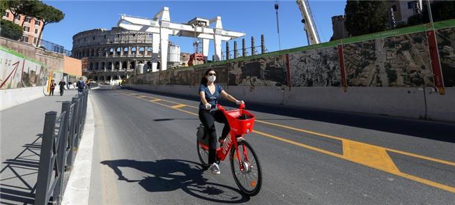 Ciclista de máscara pedala perto do Coliseu em Rom