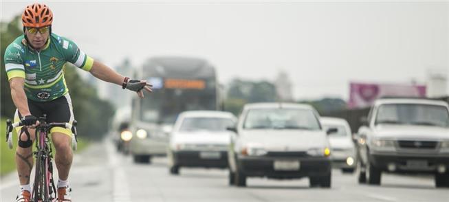 Ciclista esportivo enfrenta o trânsito para treina