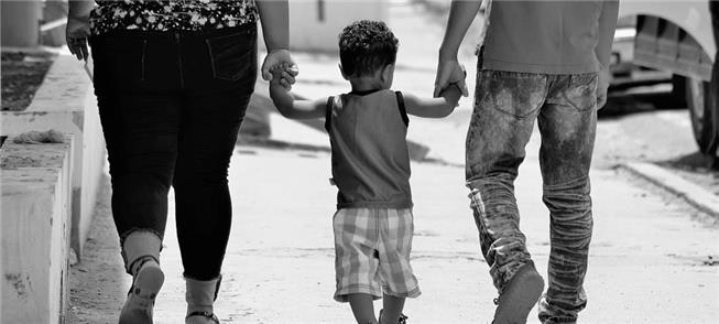 Criança caminha com seus pais
