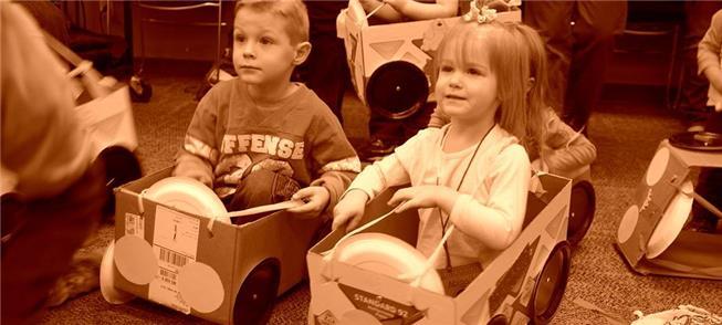 Crianças brincam de carrinhos-caixas em escola