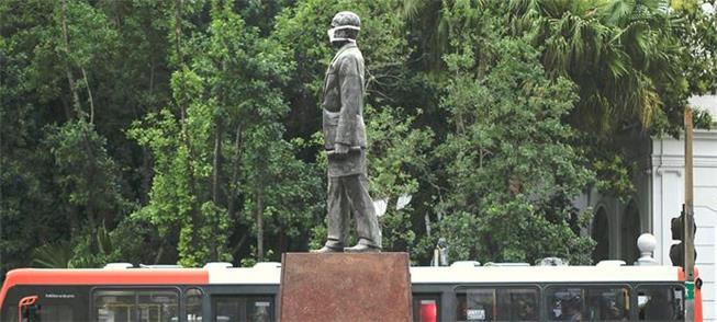 Máscaras em estátuas: protesto contra poluição em