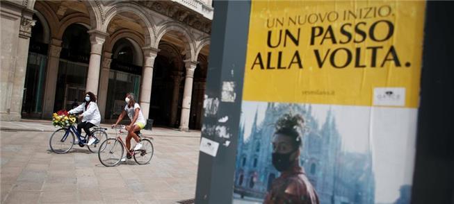 Mulheres pedalam em Milão ao final da quarentena o