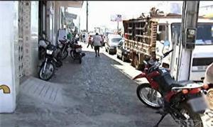 Pedestre tem calçada invadida por veículos