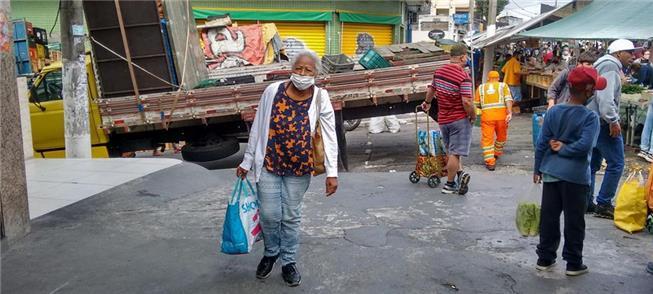 Senhora idosa carrega sacolas em uma feira de São