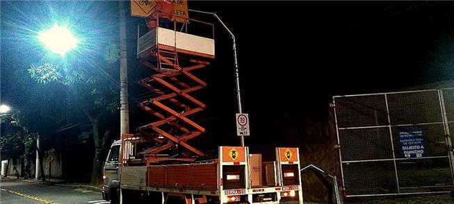 Trabalhador instala placa de sinalização em ciclor