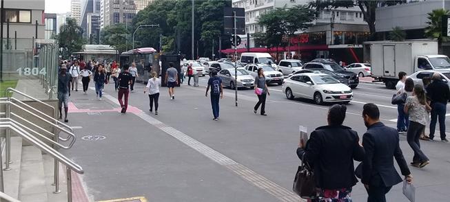 Trabalhadores caminham pela Avenida Paulista, em S