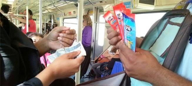 Vendedor atende cliente em carro do metrô de São P